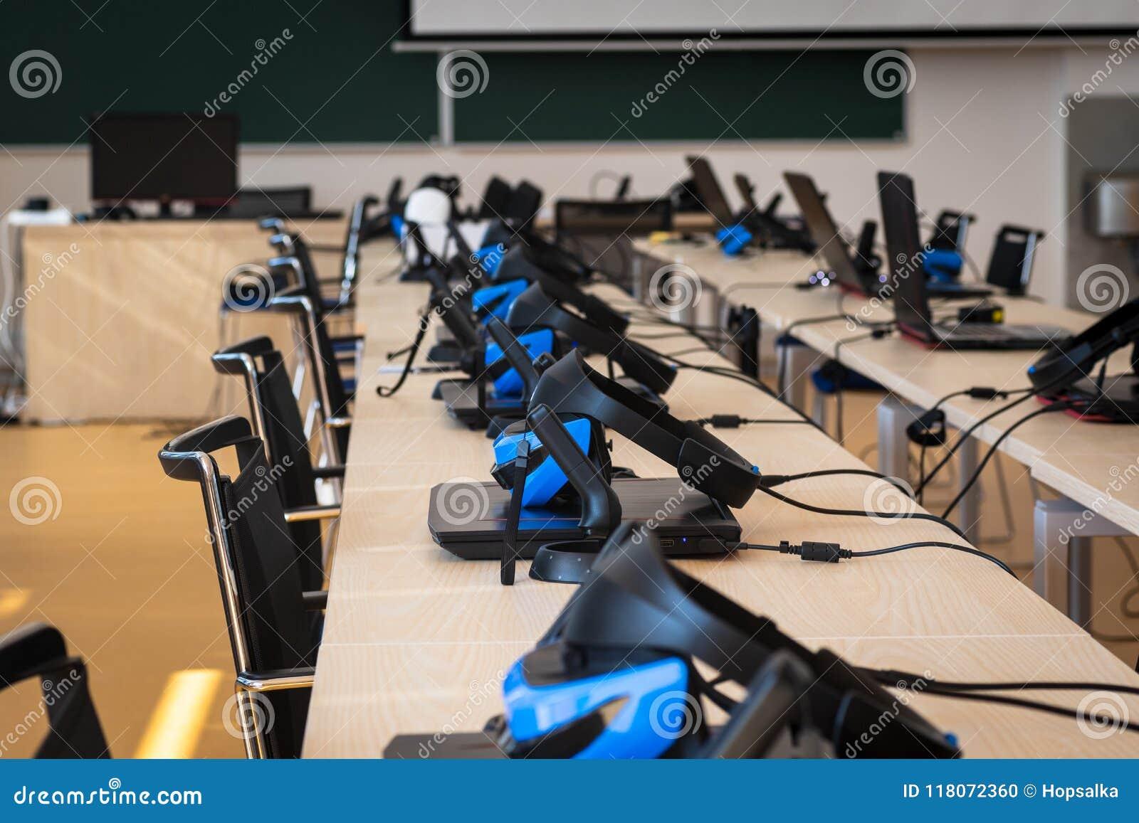 Stäng sig upp av många uppsättningar för virtuell verklighet VR i ett klassrum - hörlurar med mikrofon, kontrollant och dator