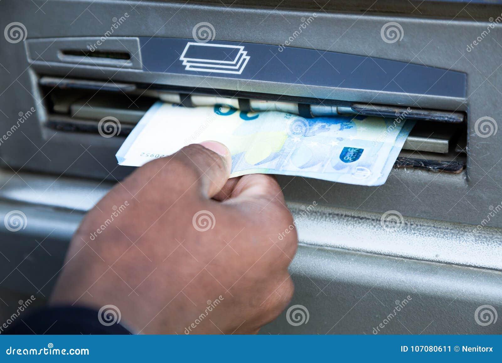 Stäng sig upp av mannen som tar kassa från ATM med kreditkorten