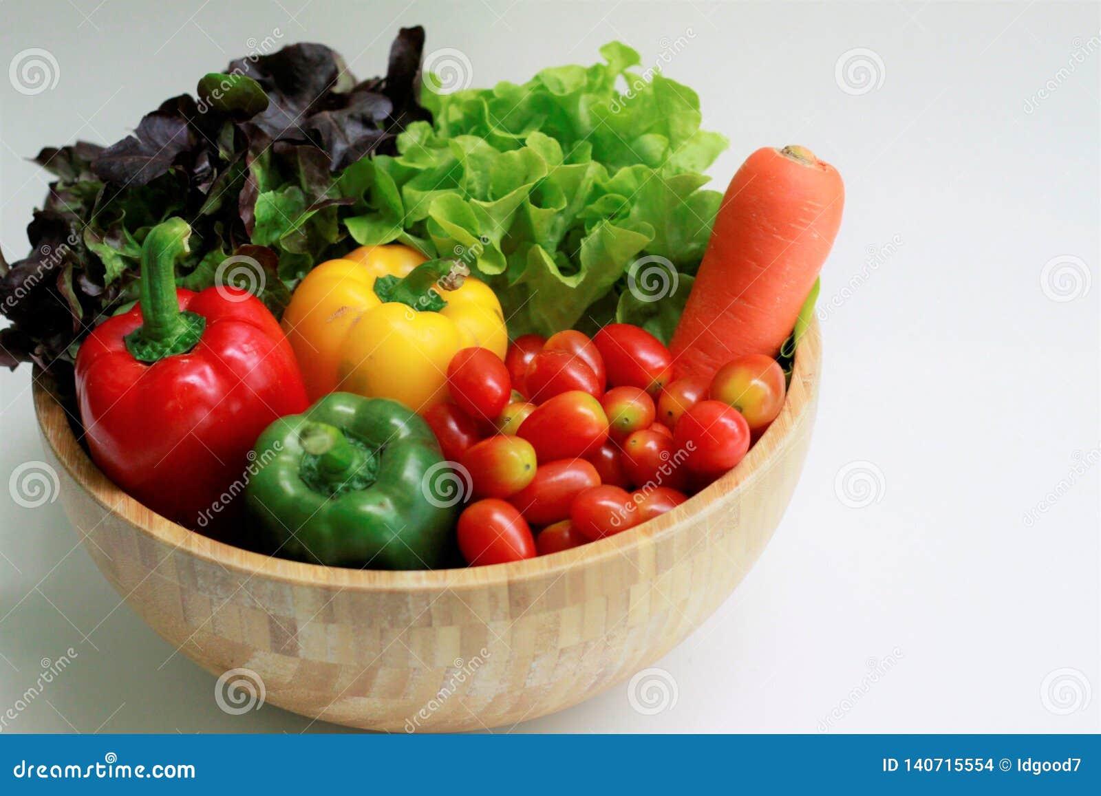 Stäng sig upp av nya grönsaker i en träbunke, den gröna eken, den röda eken, moroten, spanska peppar, körsbärsröda tomater