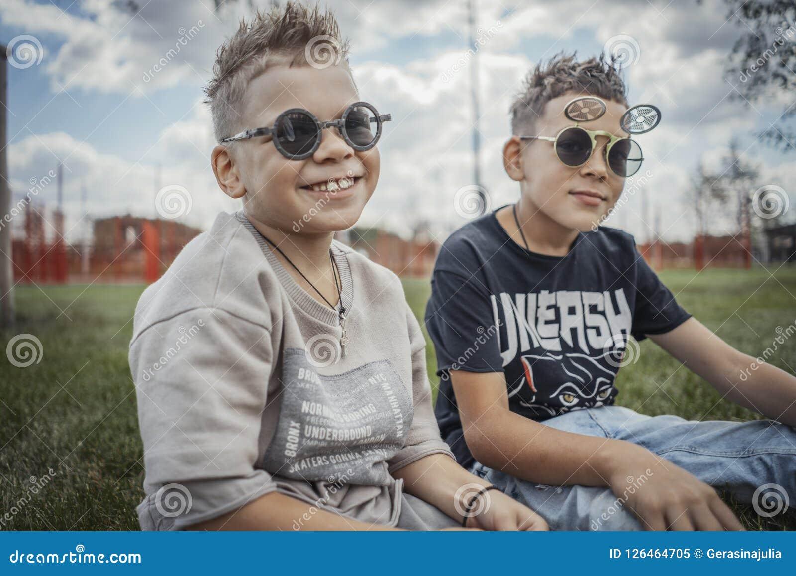 Stäng sig upp av pojkar som sitter i parkera på grönt gräs lycklig begreppsfamilj