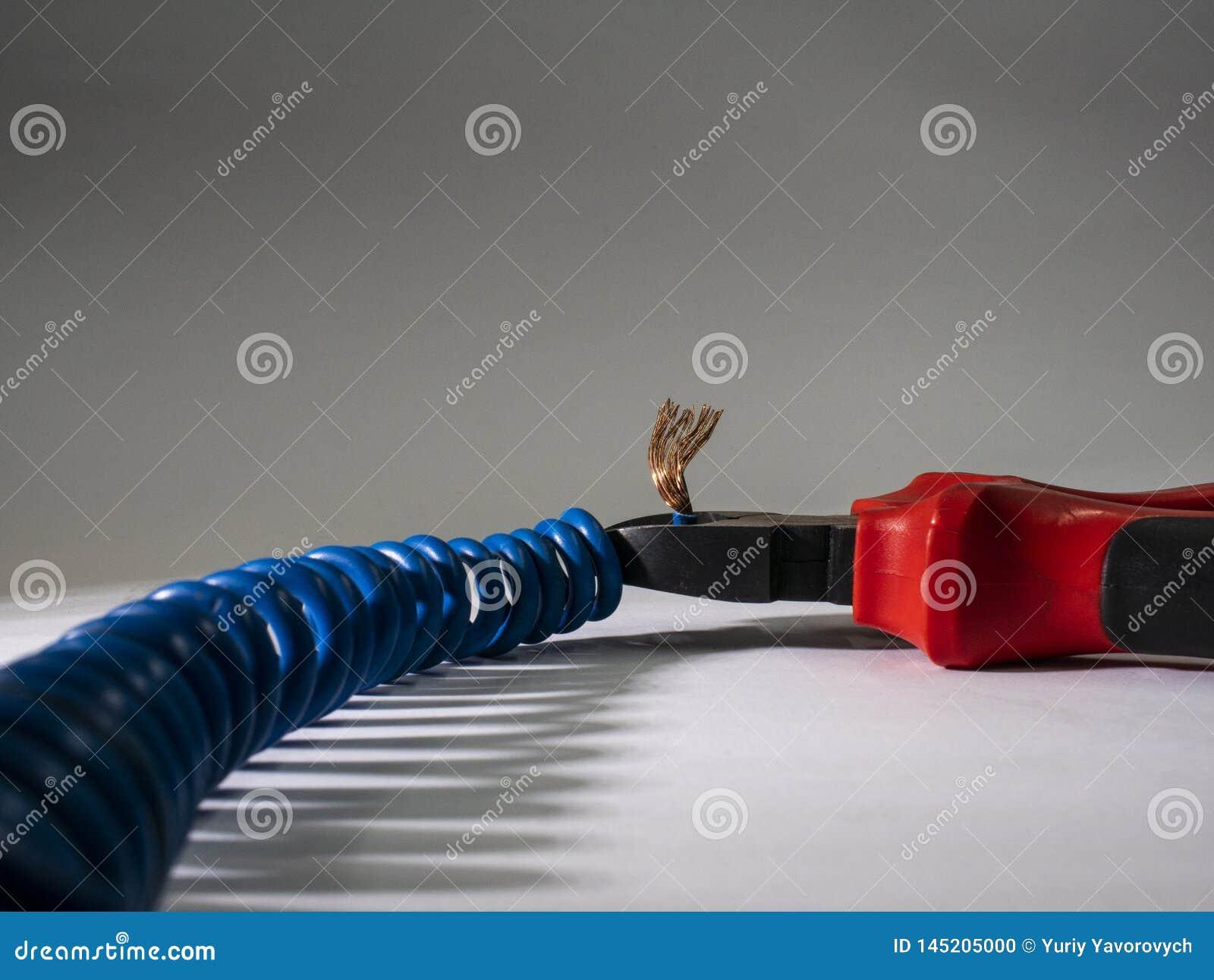 Stäng sig upp av röd plattång och blå vriden tråd på vit bakgrund Plattång som klipper kabel