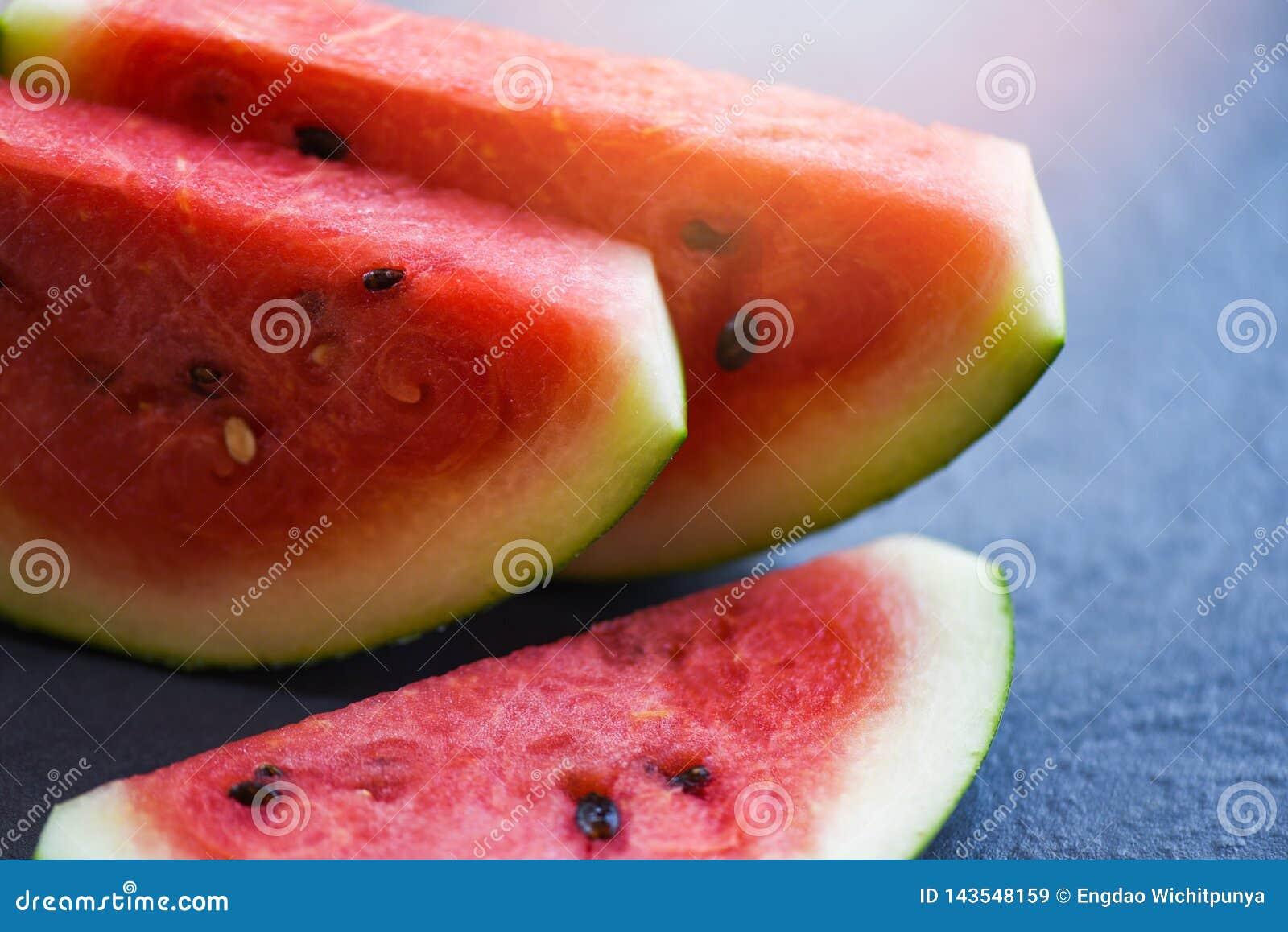 Stäng sig upp av skivavattenmelonfrukt på mörk bakgrund