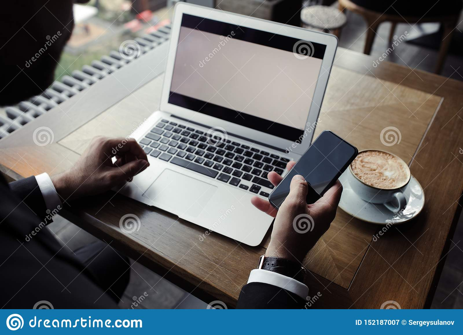Stäng sig upp av stilig affärsman och att arbeta på bärbara datorn i restaurang