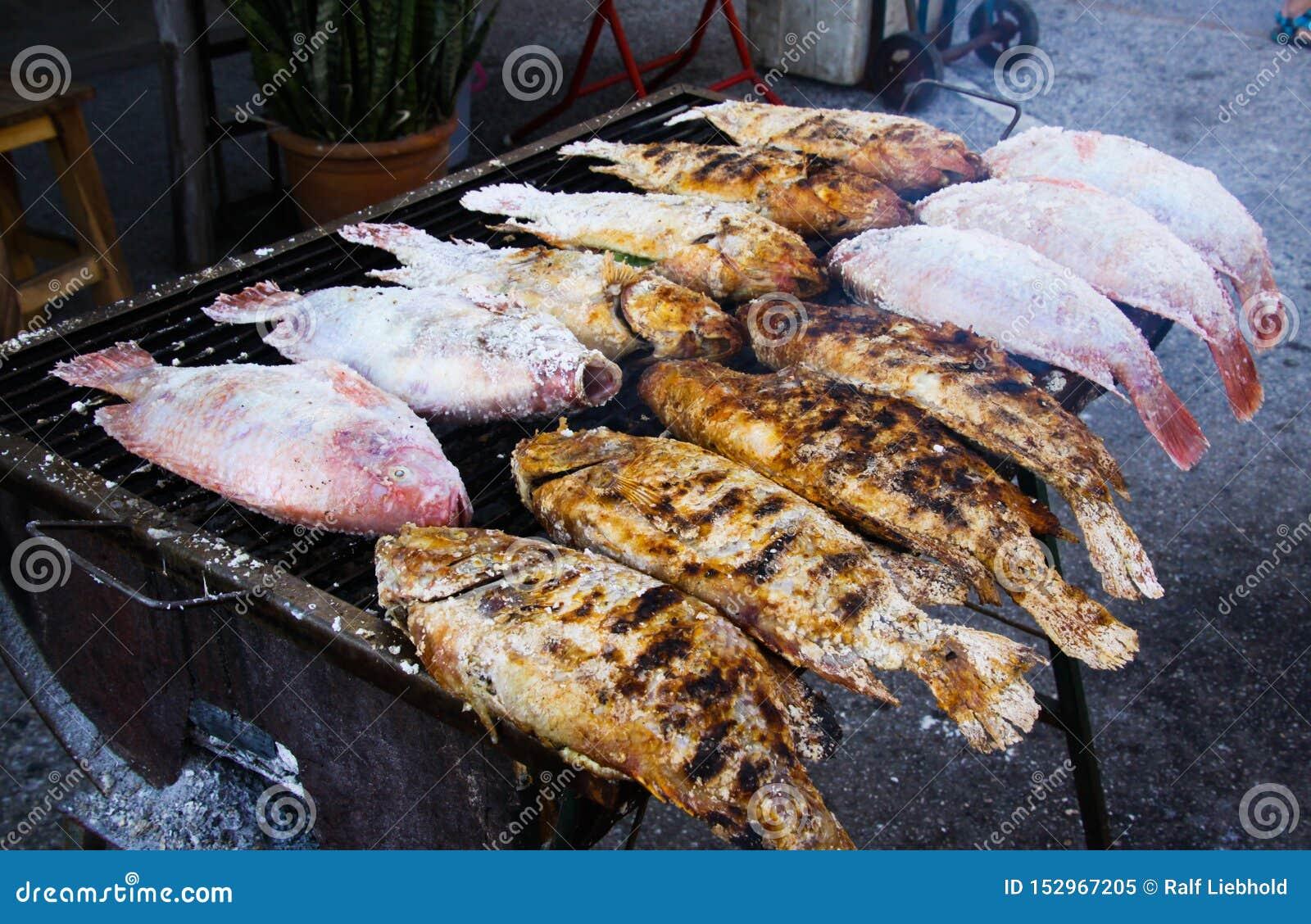 Stäng sig upp av thai gatamatgrillfest med rimmade fiskar på kolgallret - Bangkok, Thailand