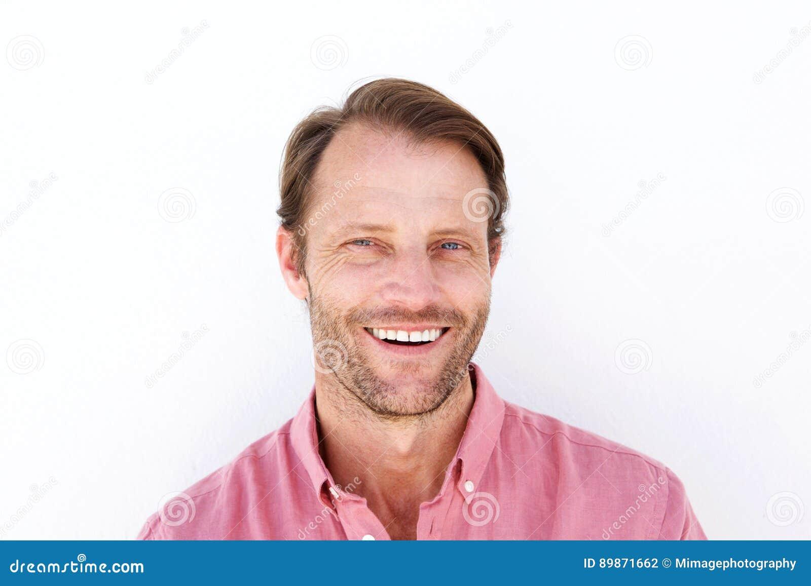Stäng sig upp den attraktiva mannen som ler mot vit bakgrund