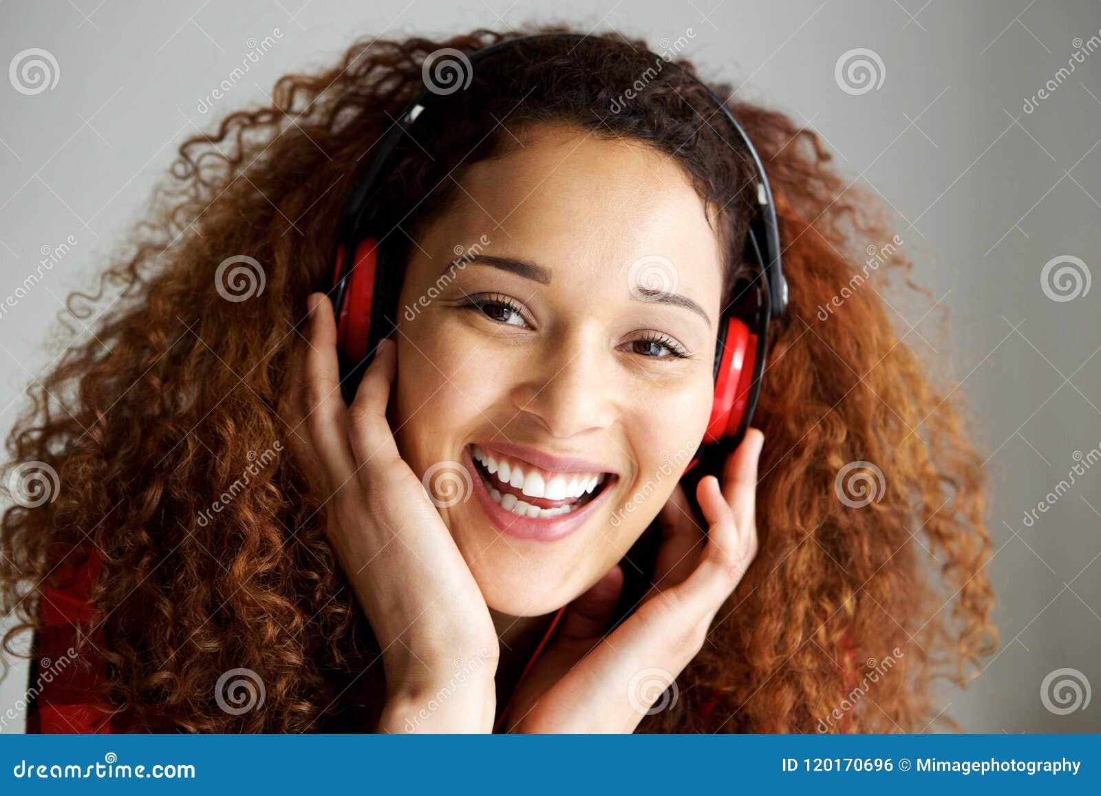 Stäng sig upp den lyckliga unga afrikansk amerikankvinnan som ler och lyssnar till musik med hörlurar