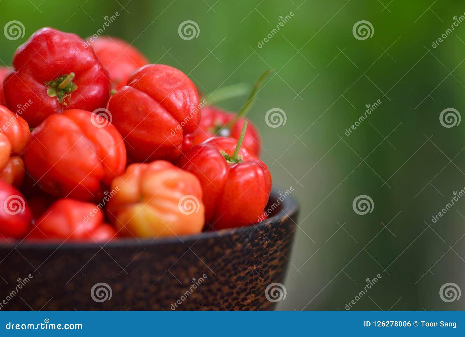 Stäng sig upp den röda Acerolakörsbäret i träbunke