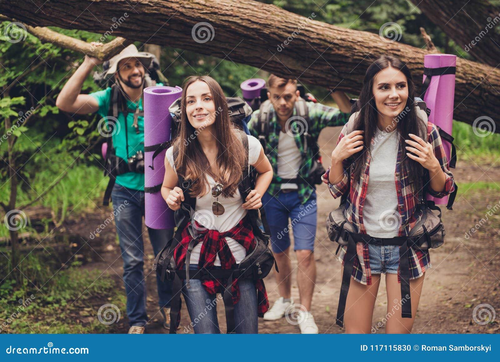 Stäng sig upp fotoet av fyra vänner som tycker om skönheten av naturen och att fotvandra i den lösa skogen som söker efter ett tr