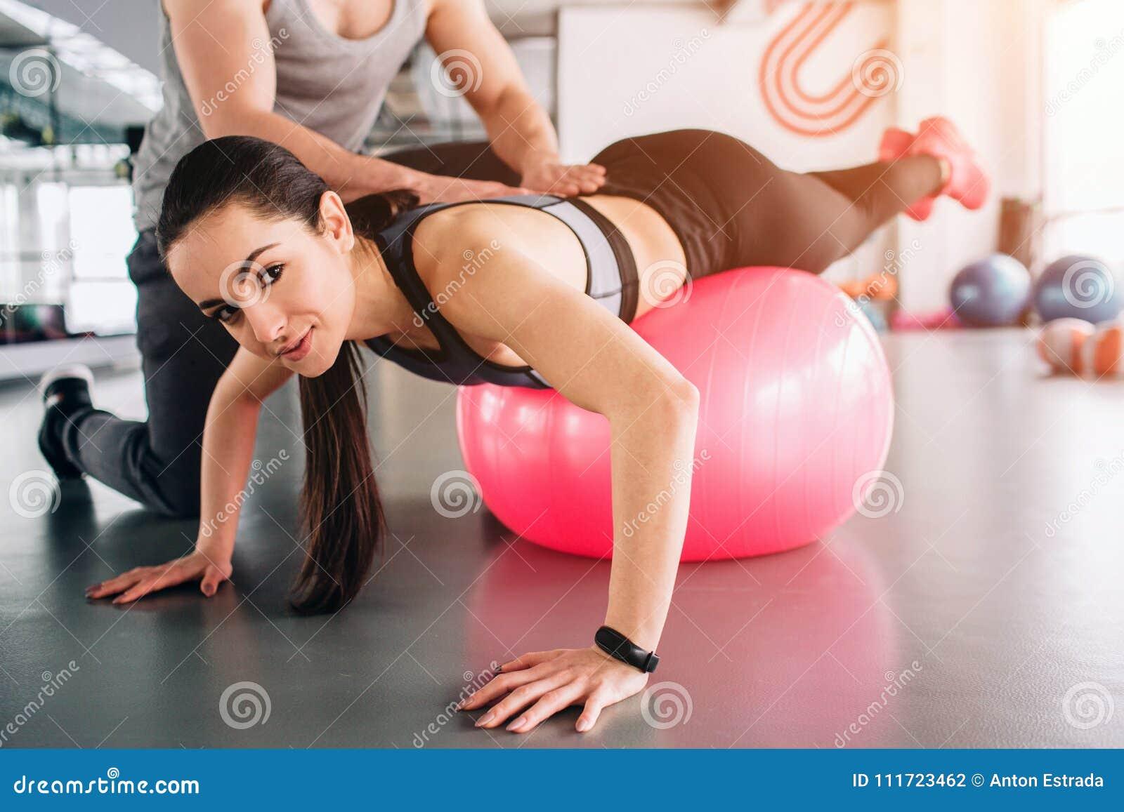 Stäng sig upp och klipp sikten av en flicka som ligger på den stora konditionbollen och ser rak framåt Hennes instruktör försöker