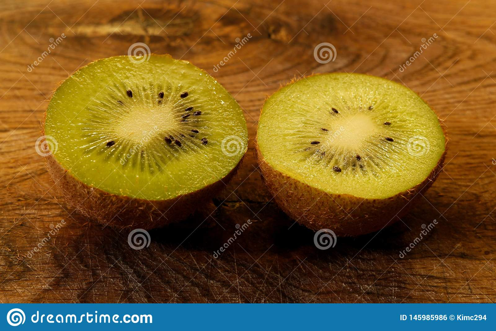 Stäng sig upp på en kiwifruit som delas i halva på en träskärbräda Ljust - grön kiwi med svart frö