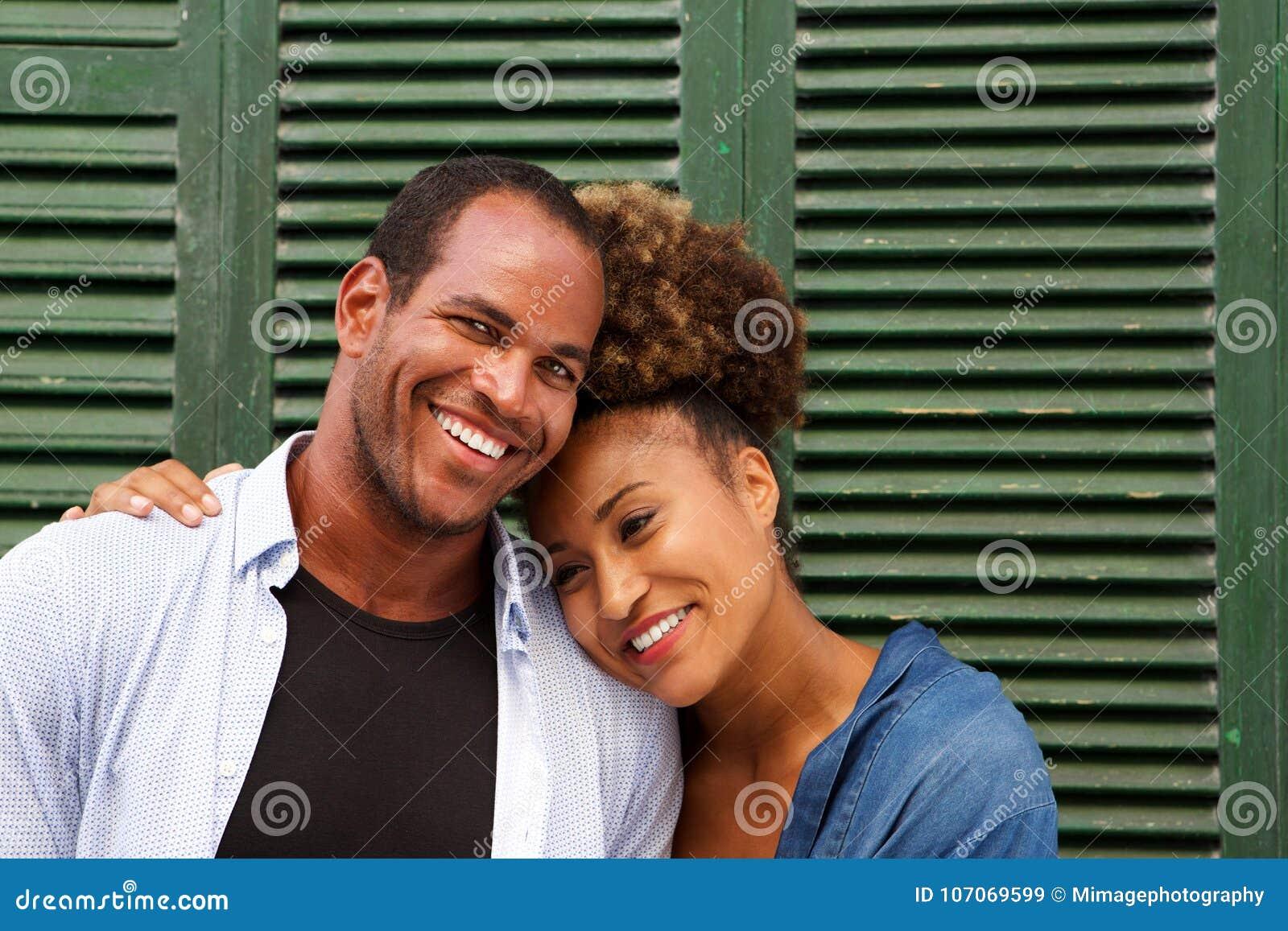Stäng sig upp romantiska attraktiva par, i att skratta för omfamning