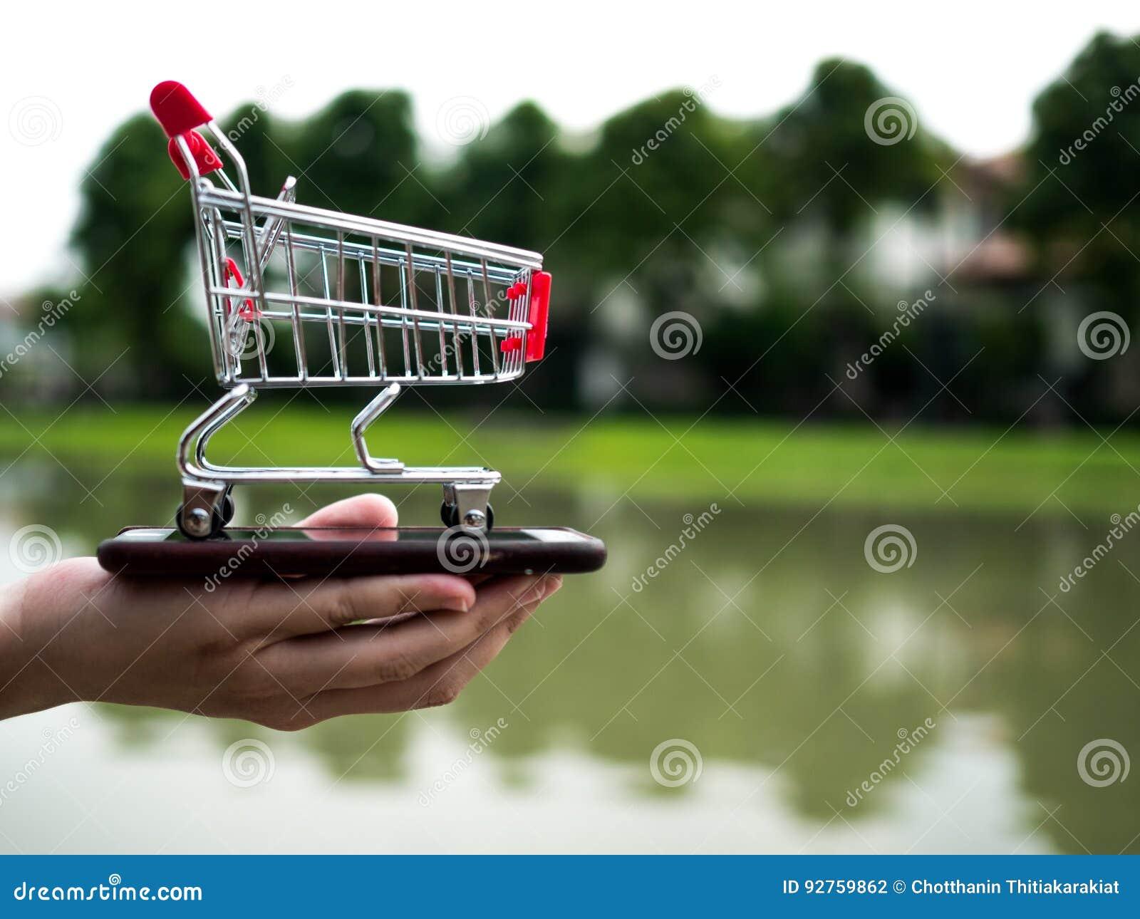 Stäng sig upp shoppingvagnen på mobiltelefonen, affär i eCommercebegrepp