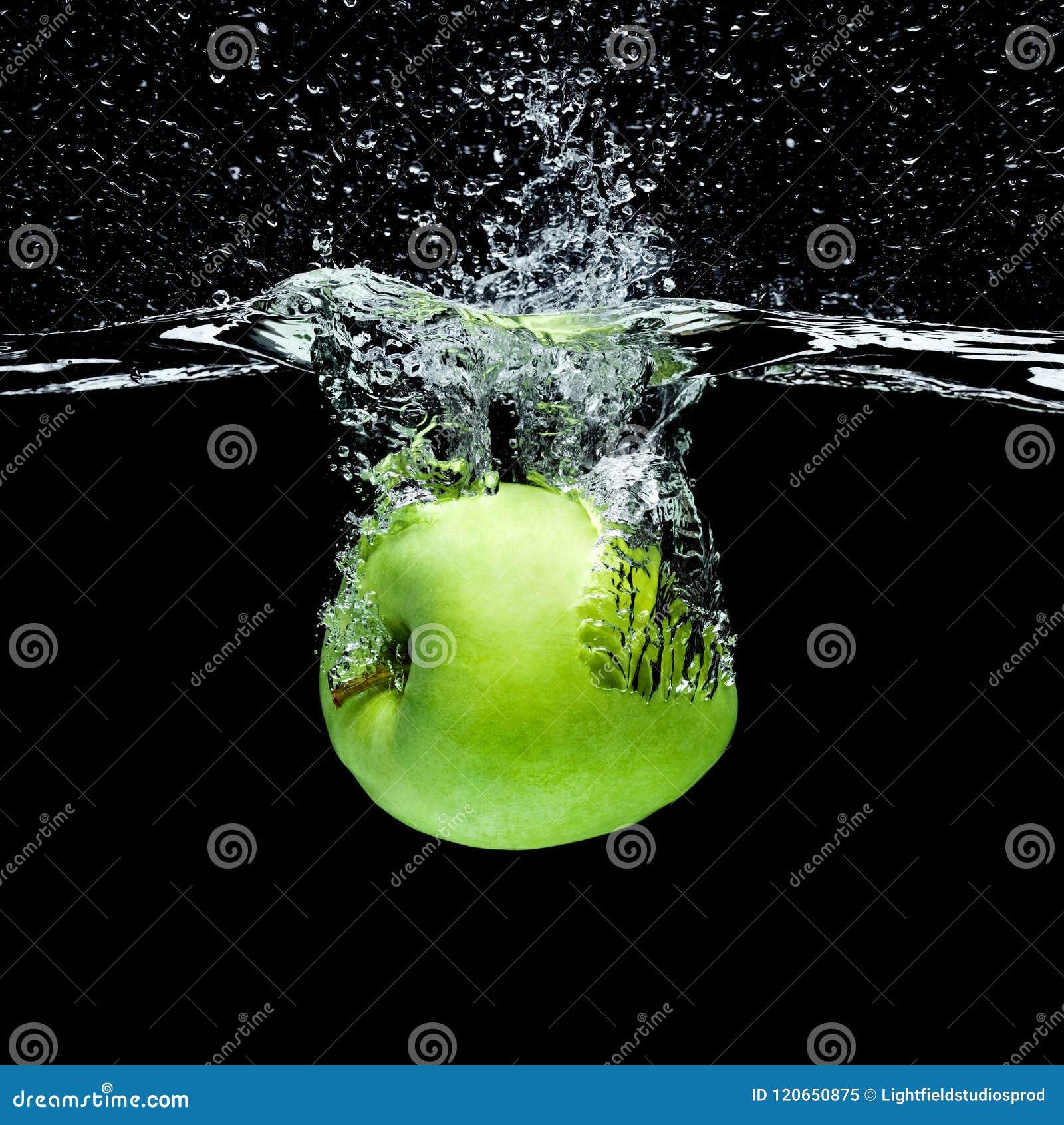 Stäng sig upp sikten av det gröna äpplet som faller in i vatten