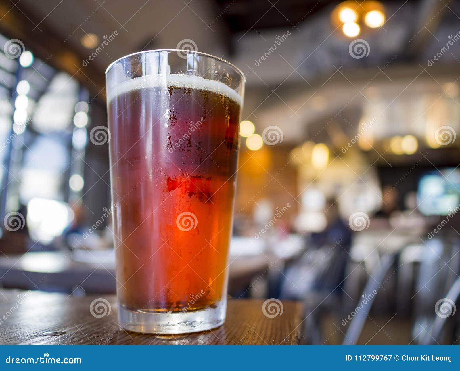 Stäng sig upp skott av ett exponeringsglas av kallt öl