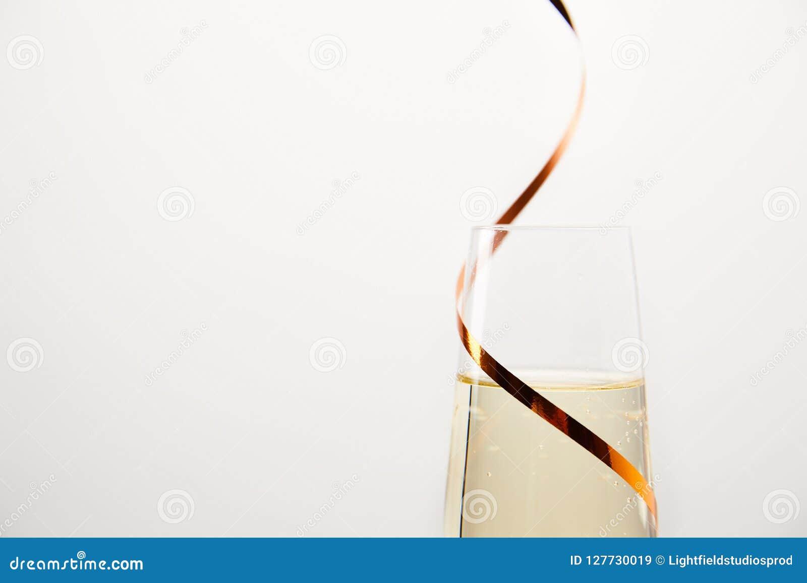 Stäng sig upp skottet av champagneexponeringsglas som slås in av bandet som isoleras på vit bakgrund, feriebegrepp