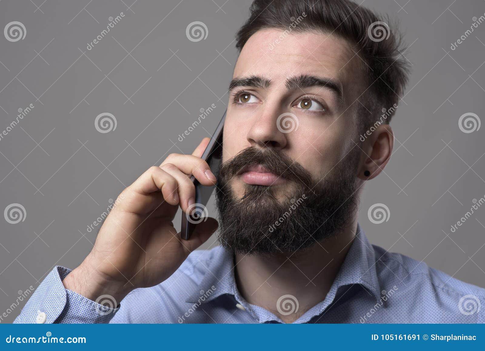 Stäng sig upp ståenden av den barn uppsökte affärsmannen som talar på mobiltelefonen som ser upp på copyspace
