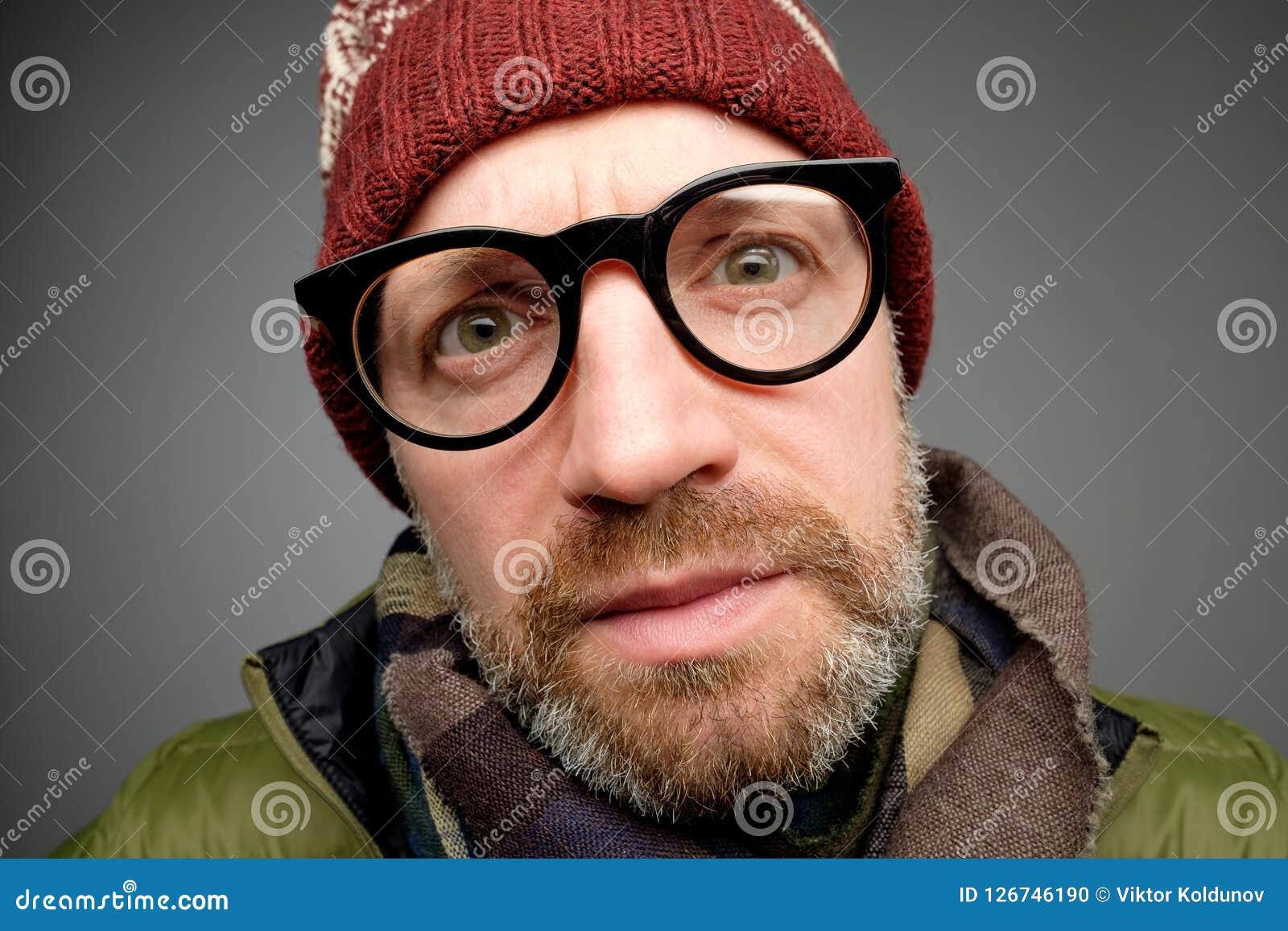 Stäng sig upp ståenden av mitt åldrades europeammannen i rolig varm hatt och exponeringsglas som märker den dolde kameran