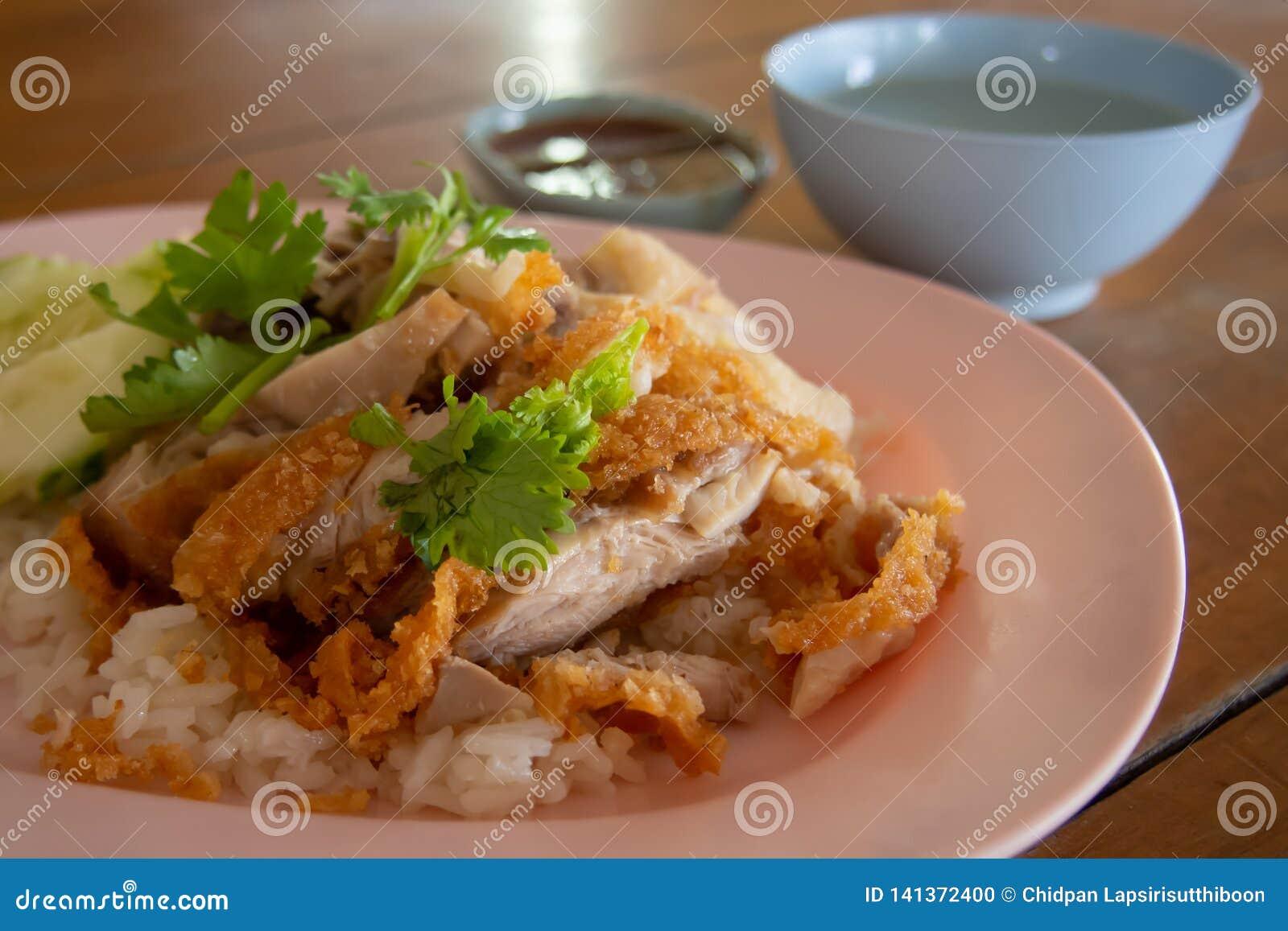 Stäng sig upp stekt kycklingris i en platta och strila med koriander Med feg buljong och en kopp av doppa sås på ett trä