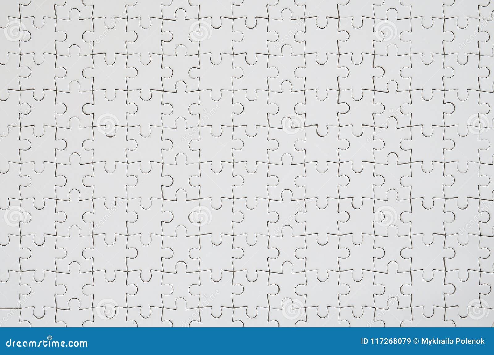 Stäng sig upp textur av ett vitt pussel i församlat villkor Top beskådar Många delar av en stor hel mosaik förenas