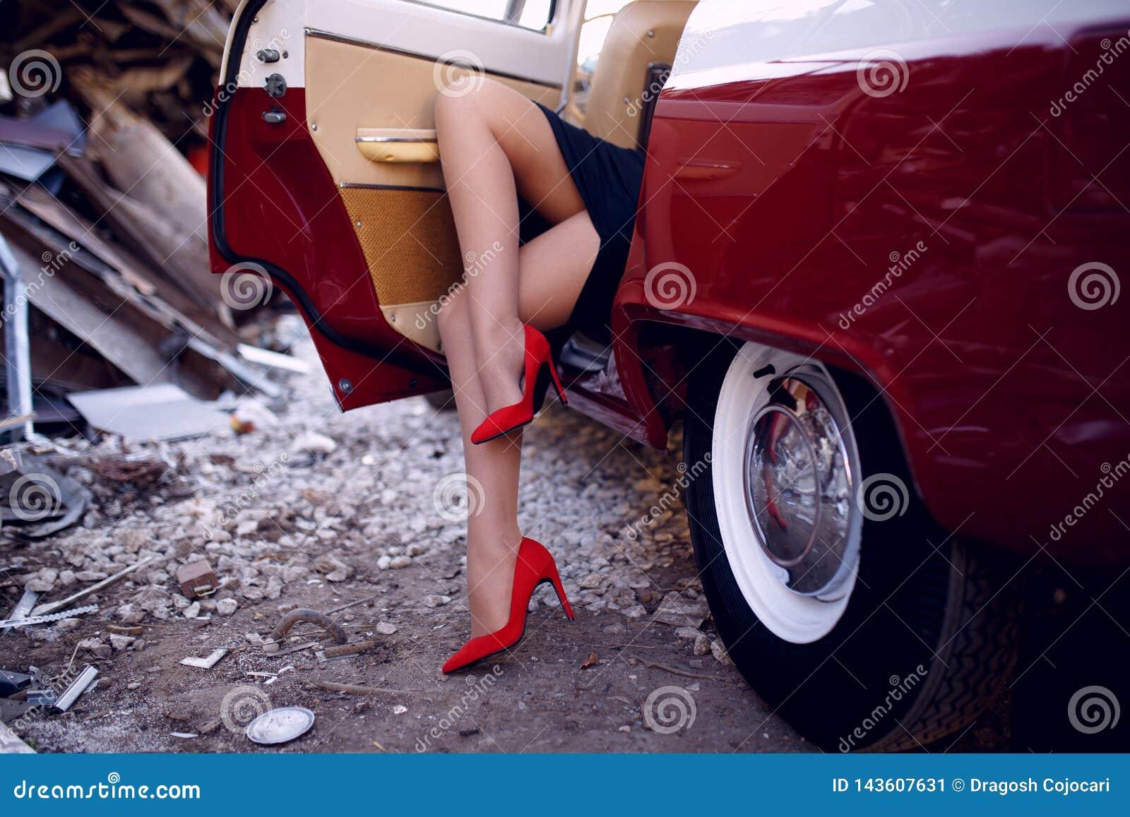 Stäng upp av kvinnaben i röda skohäl som sitter inom på den röda bilen för tappning på järnförrådsplatsbakgrund den konstnärliga