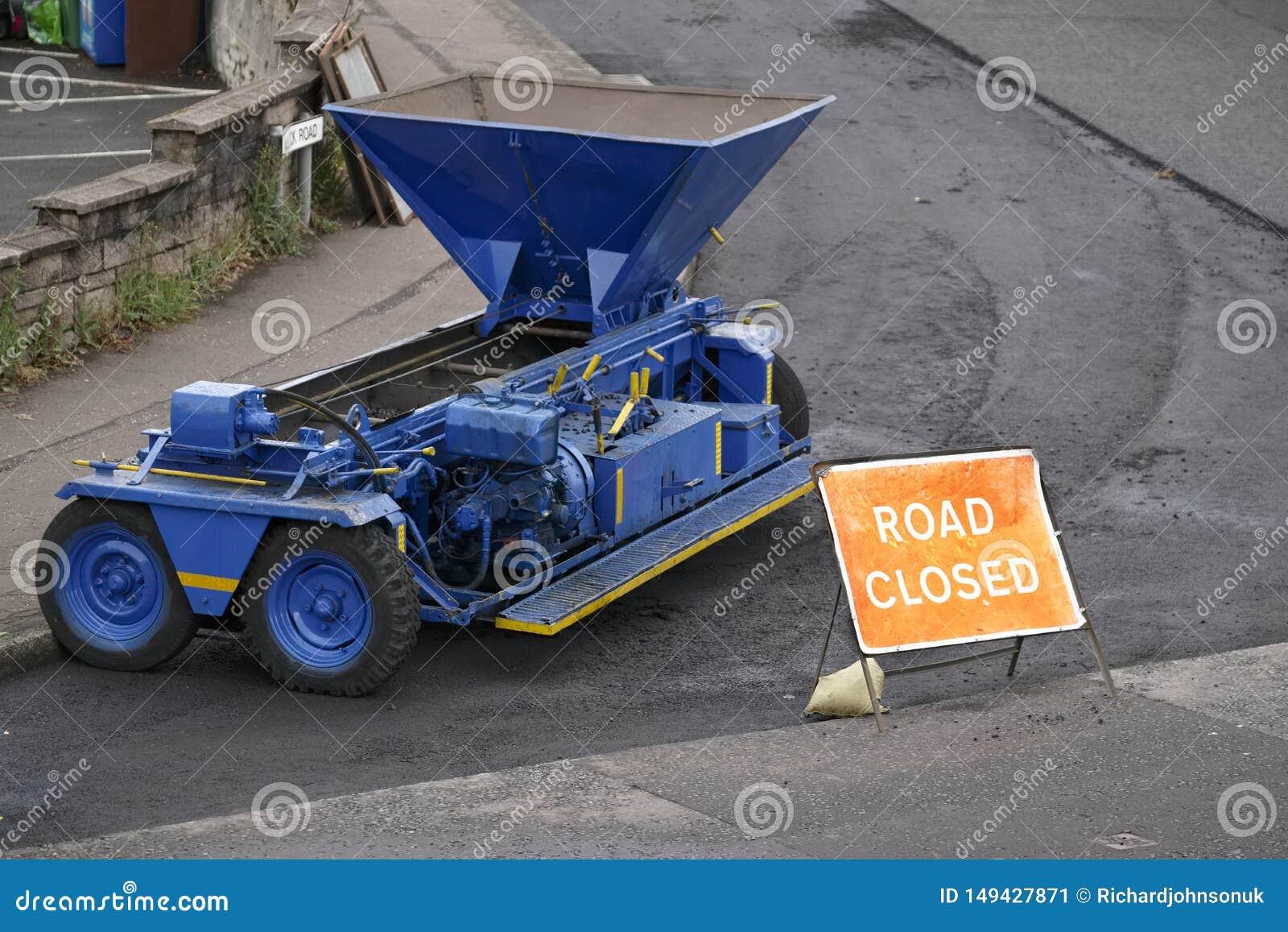 Stängd tecken och reparation för väg till tjäraasfaltgatan med den blåa maskinen