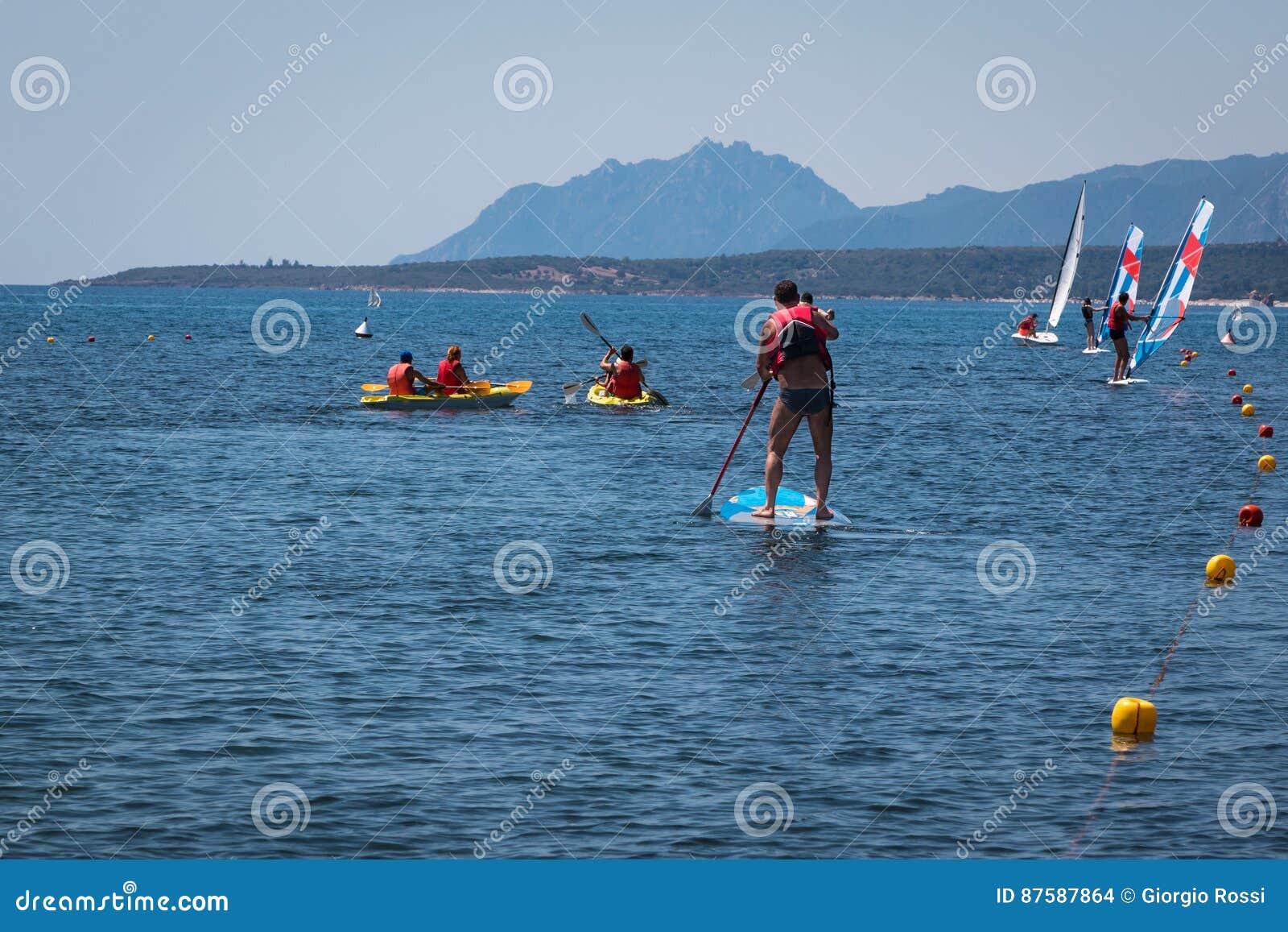 Stå upp surfaremannen Paddleboarding ombord bland kanoter och seger