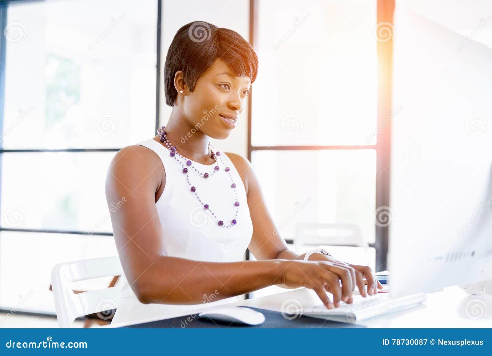 Stående av affärskvinnan som i regeringsställning arbetar på hennes skrivbord