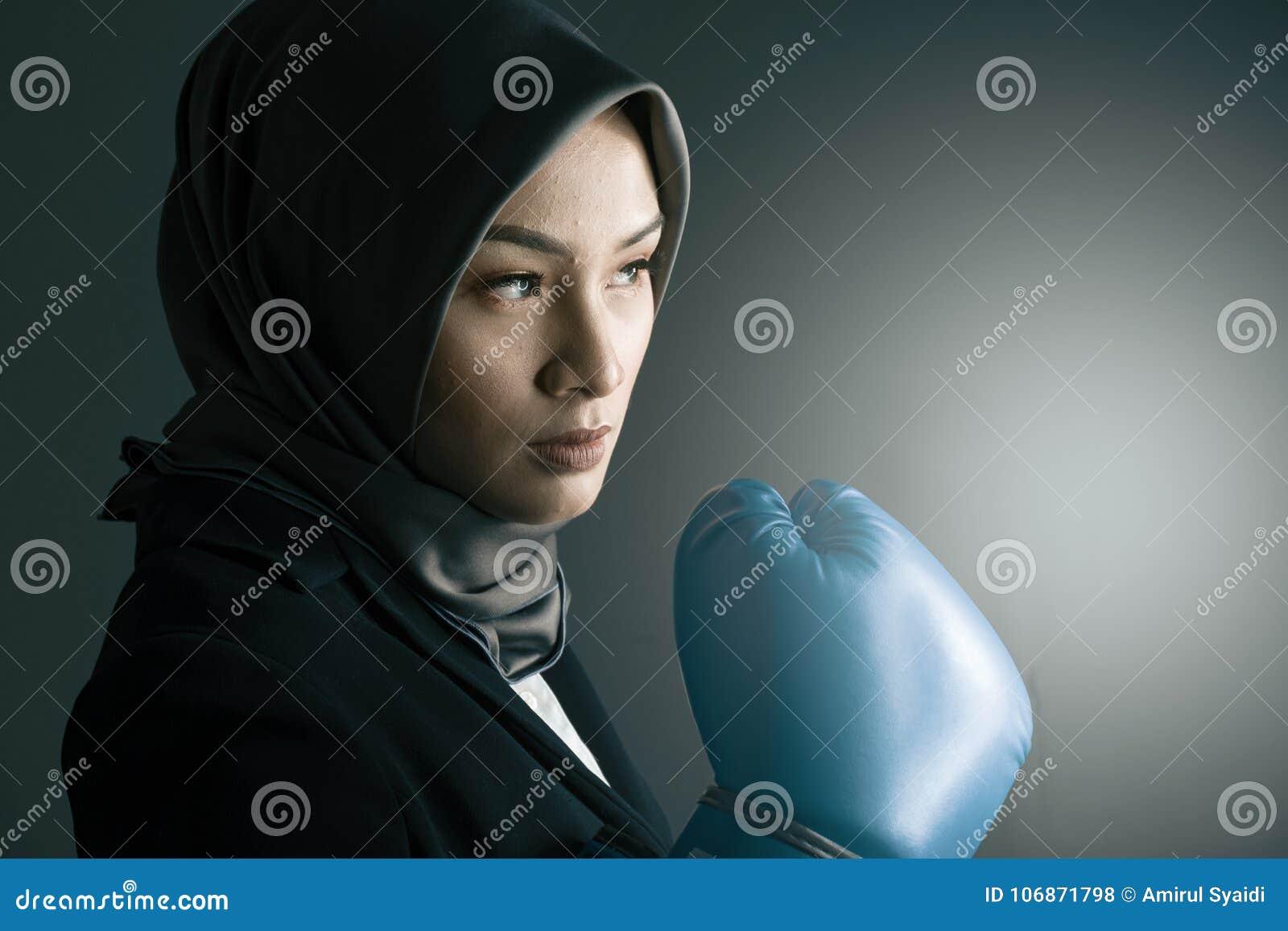 Stående av aggressivt och säkert uttrycksbarn som grinar den bärande boxninghandsken för yrkesmässig kvinna
