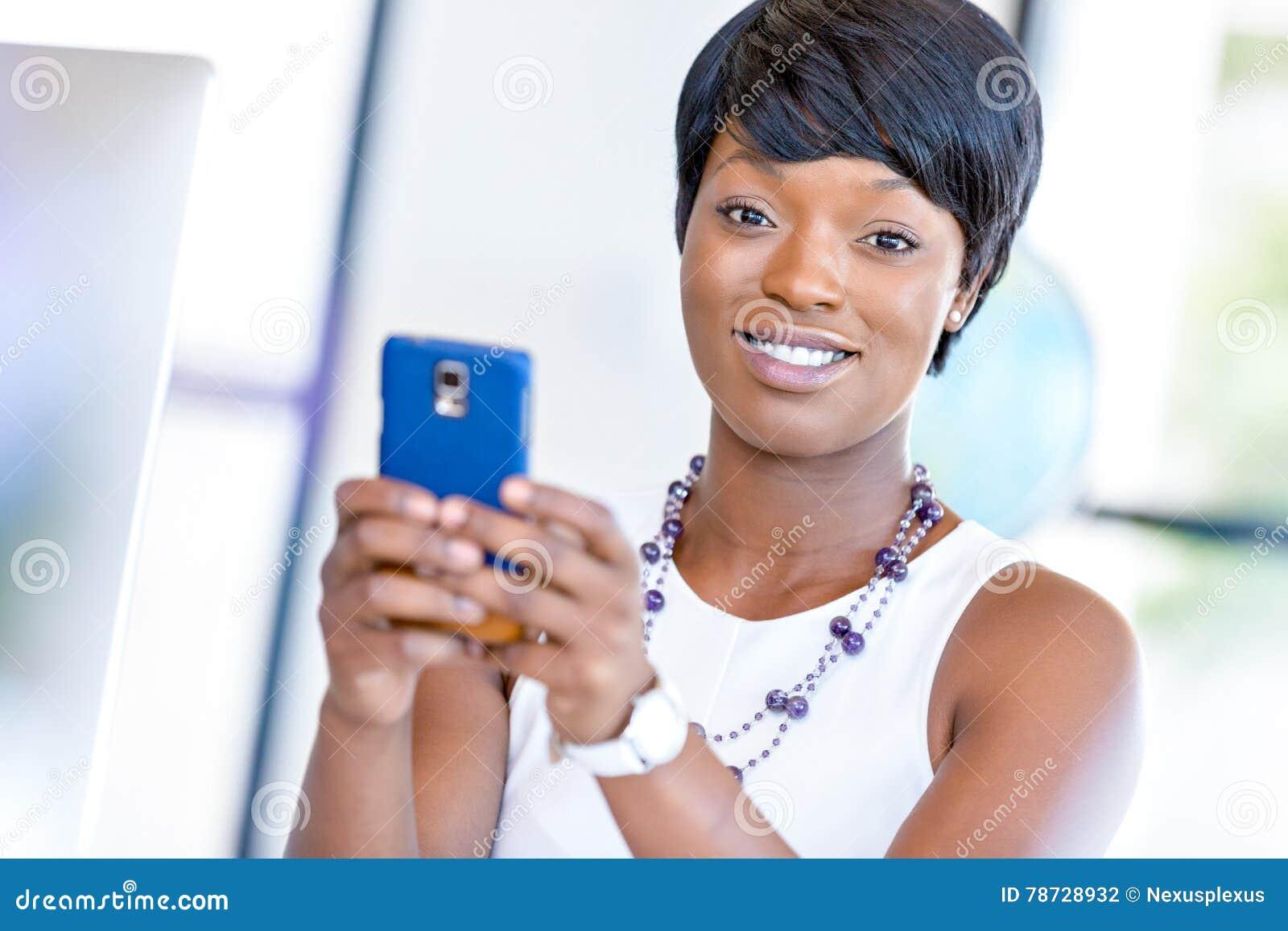 Stående av att le affärskvinnan med mobilen
