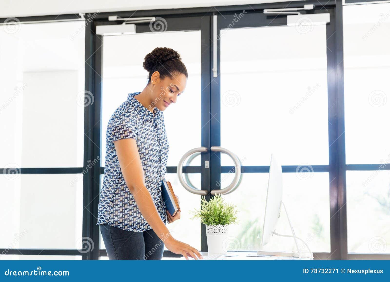 Stående av att le anseende för afro--amerikan kontorsarbetare i offfice