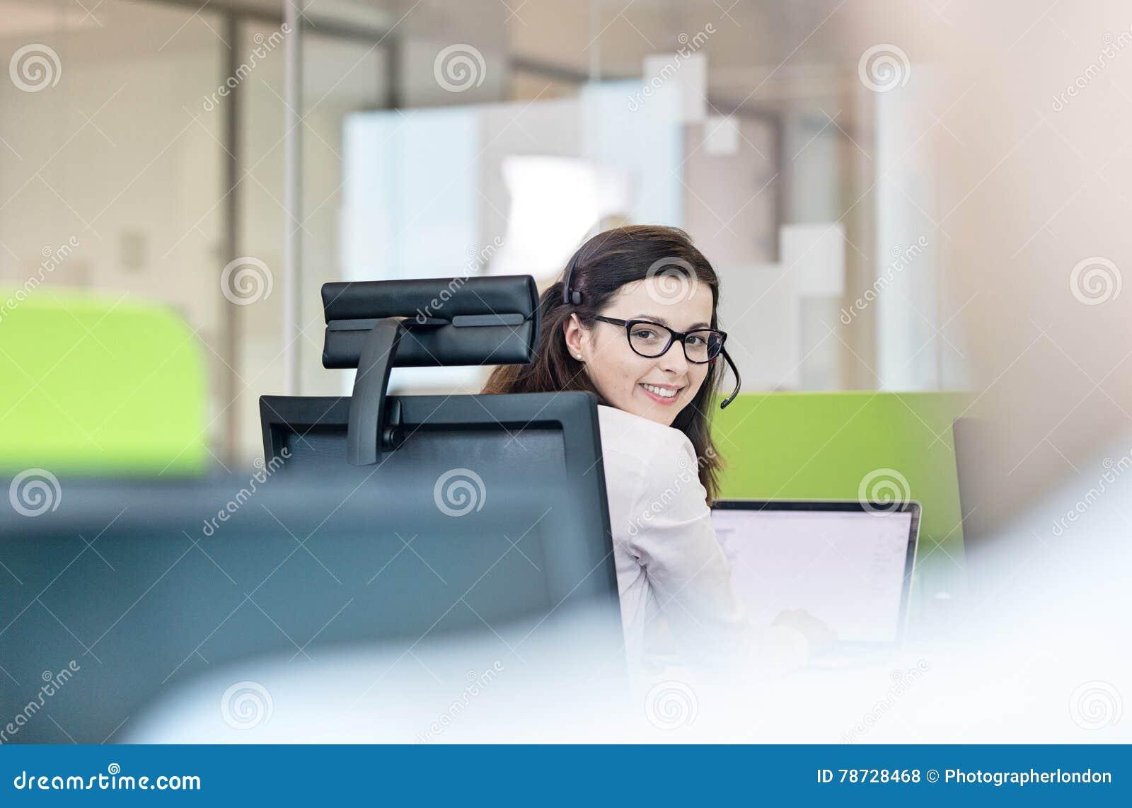 Stående av att le den bärande hörlurar med mikrofon för ung affärskvinna i regeringsställning
