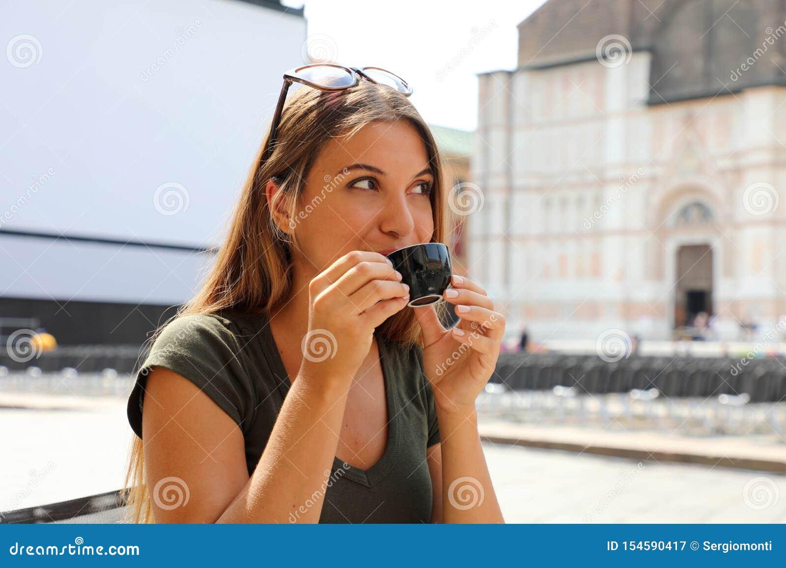 Stående av att le den härliga kvinnan som sitter i det friakafé i Italien som dricker kaffe