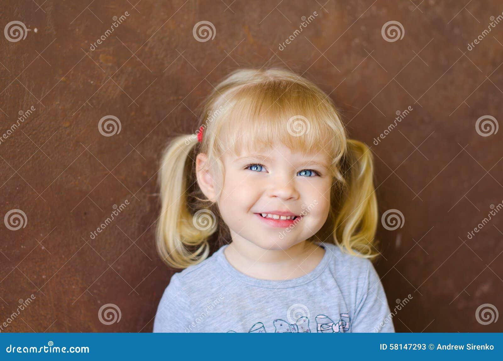Stående av att le den lilla gulliga blonda flickan
