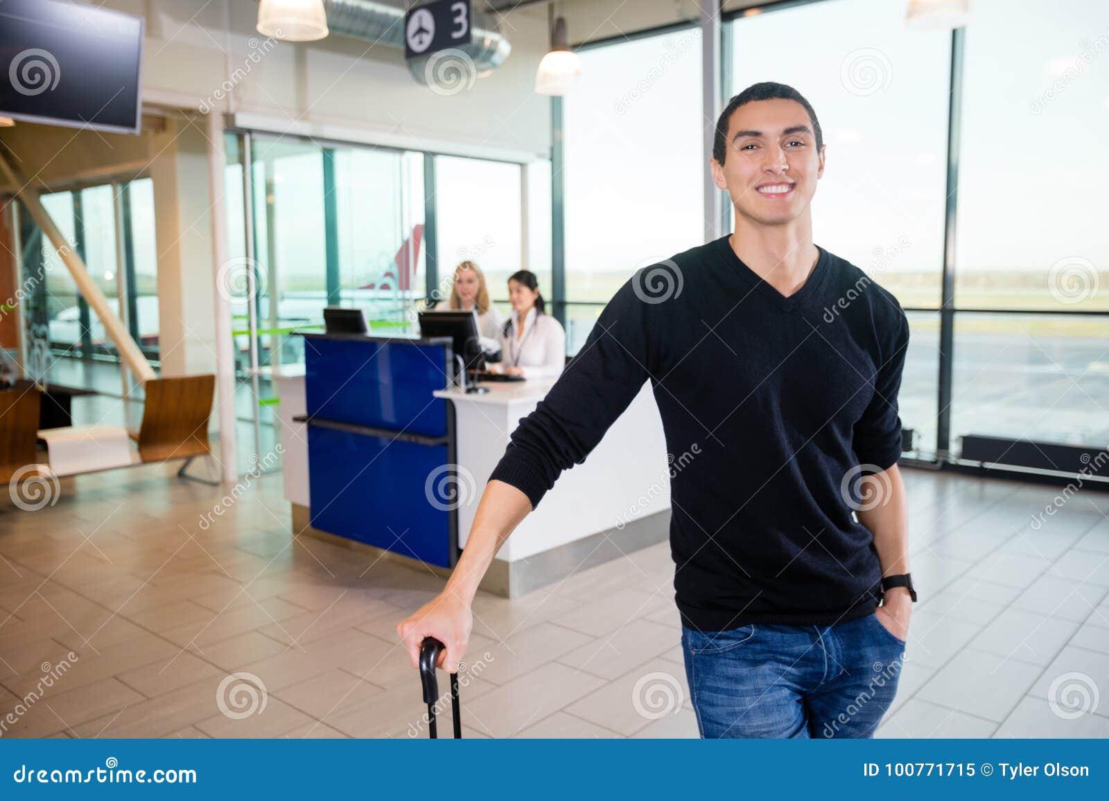 Stående av att le den manliga passageraren på flygplatsen