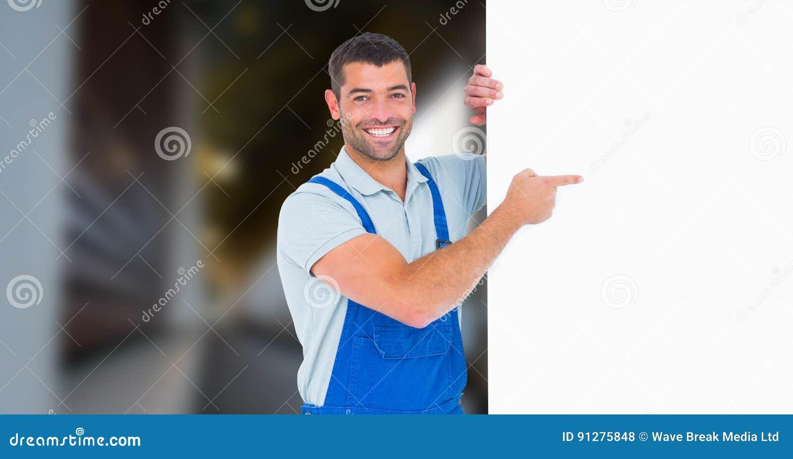 Stående av att le den manuella arbetaren som pekar på den tomma affischtavlan