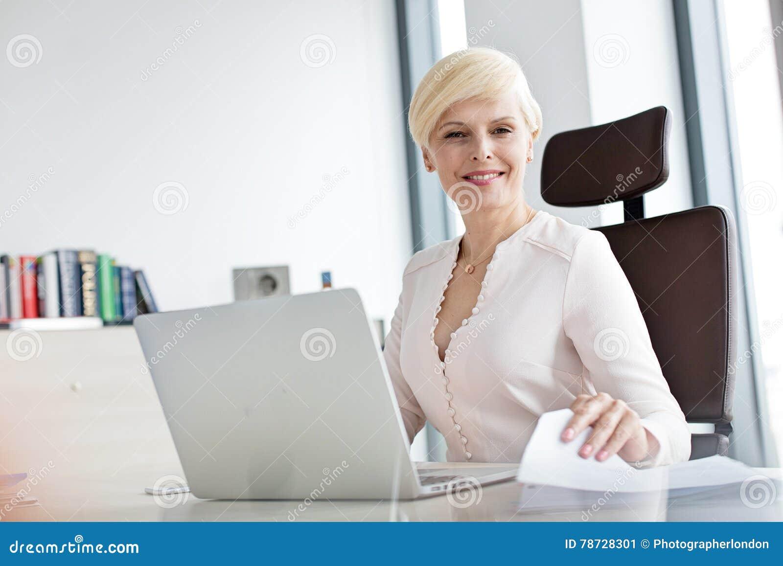 Stående av att le den mogna affärskvinnan med bärbara datorn och dokumentet på kontorsskrivbordet