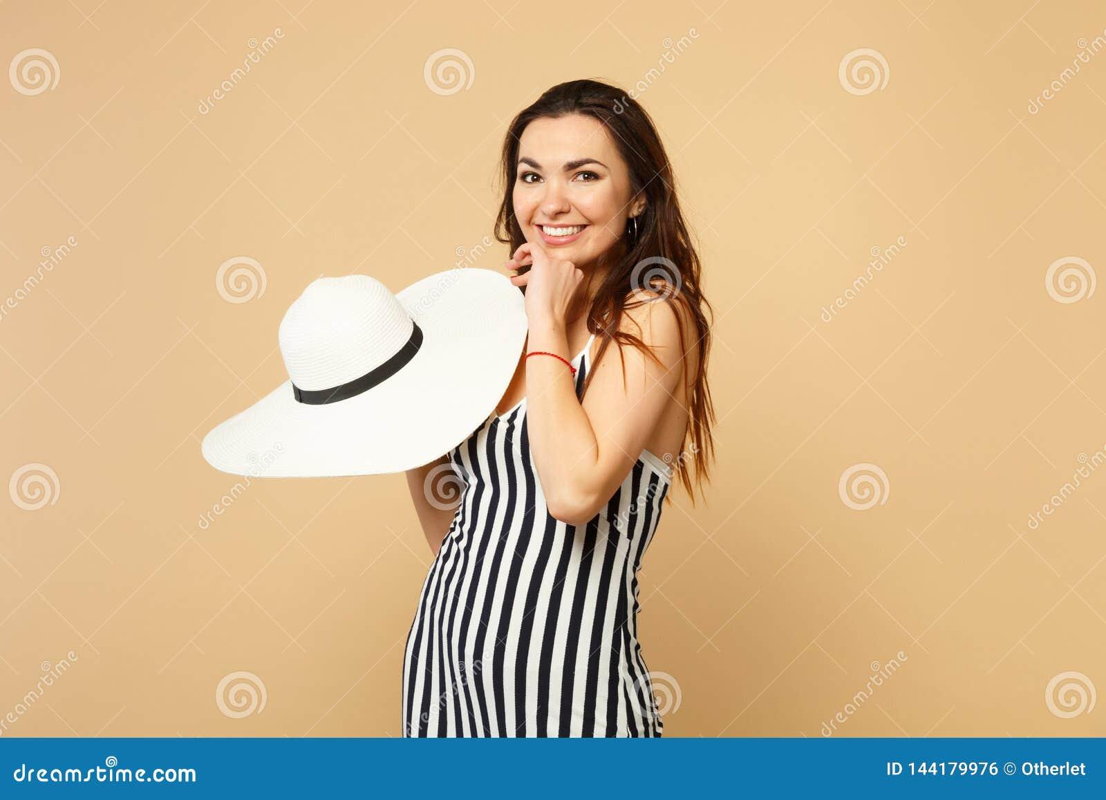 Stående av att le den nätta unga kvinnan i svartvit randig klänninginnehavhatt som ser kameran på pastell