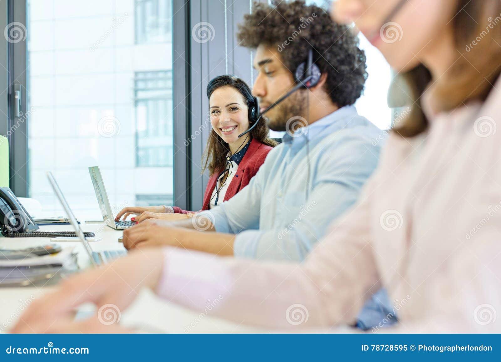 Stående av att le den unga affärskvinnan som använder hörlurar med mikrofon och bärbara datorn med kollegor i förgrund på kontore