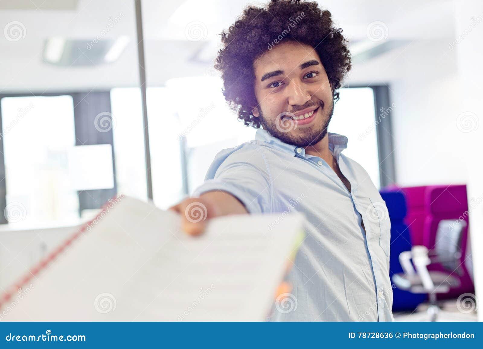 Stående av att le den unga affärsmannen som i regeringsställning ger dokumentet