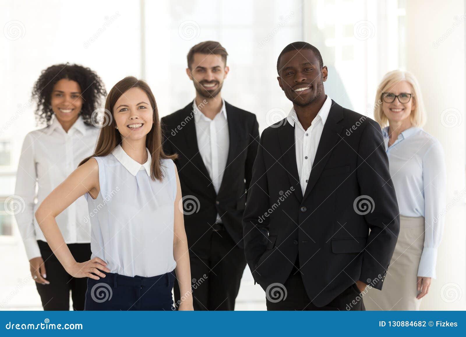 Stående av att le det olika arbetslaganseendet som i regeringsställning poserar
