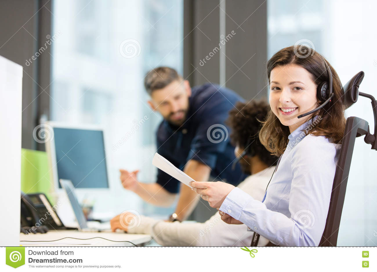 Stående av att le dokument för innehav för kundtjänstrepresentant med kollegor i bakgrund på kontoret