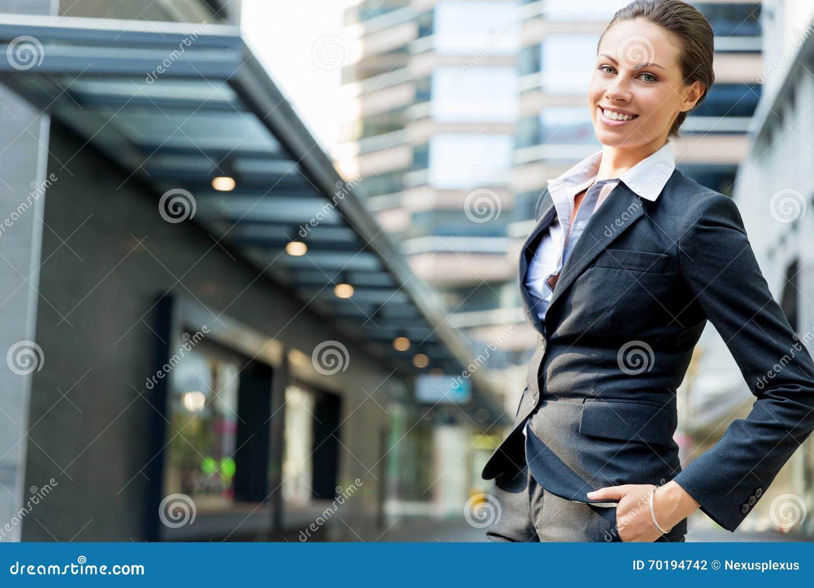 Stående av att le för affärskvinna som är utomhus-