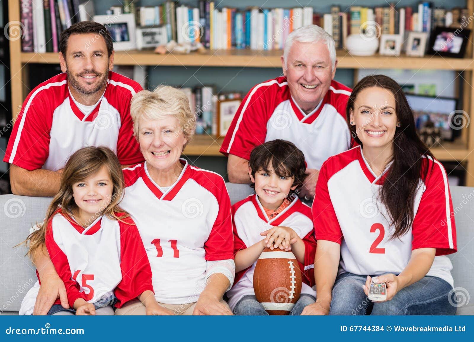 Stående av att le familjen med morföräldrar som håller ögonen på den amerikanska fotbollsmatchen