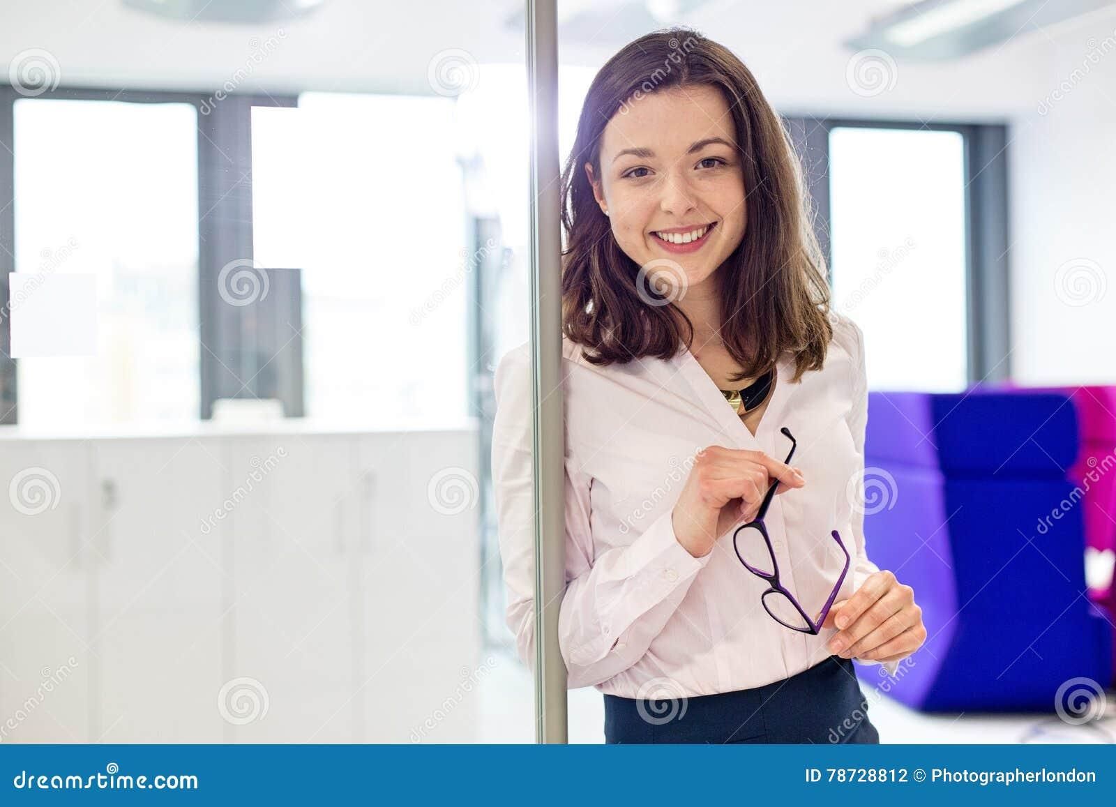 Stående av att le hållande glasögon för ung affärskvinna i regeringsställning