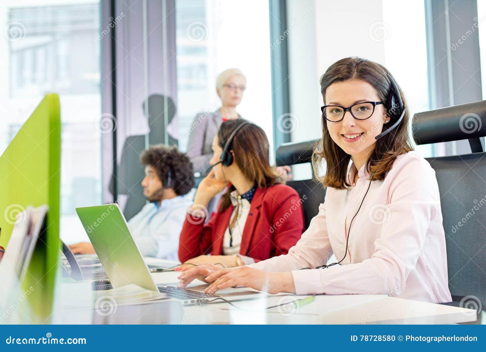 Stående av att le kundtjänstrepresentanten genom att använda bärbara datorn medan kollegor i bakgrund på kontoret