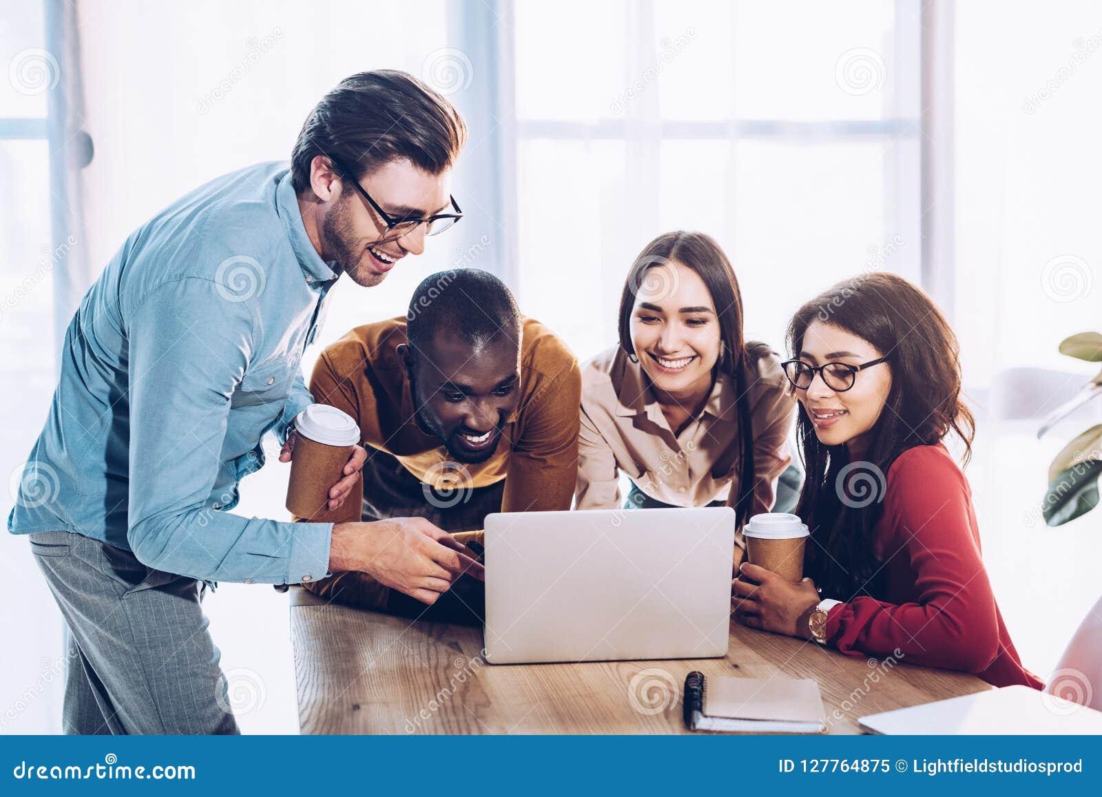 Stående av att le mångkulturellt affärsfolk som tillsammans arbetar på bärbara datorn