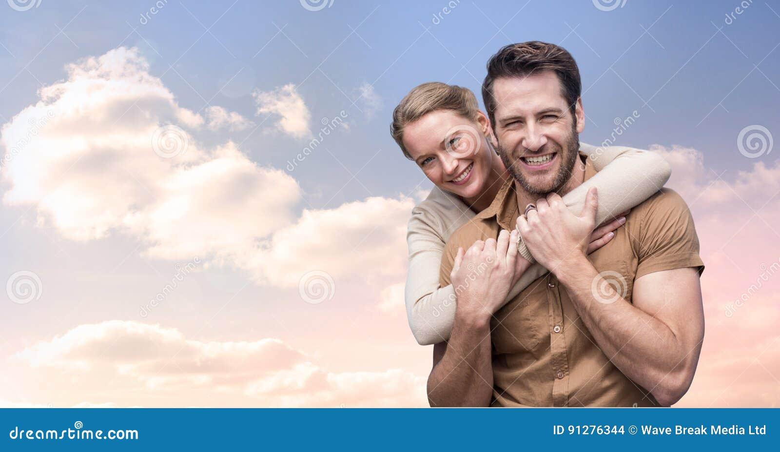 Stående av att le par som omfamnar mot molnig himmel