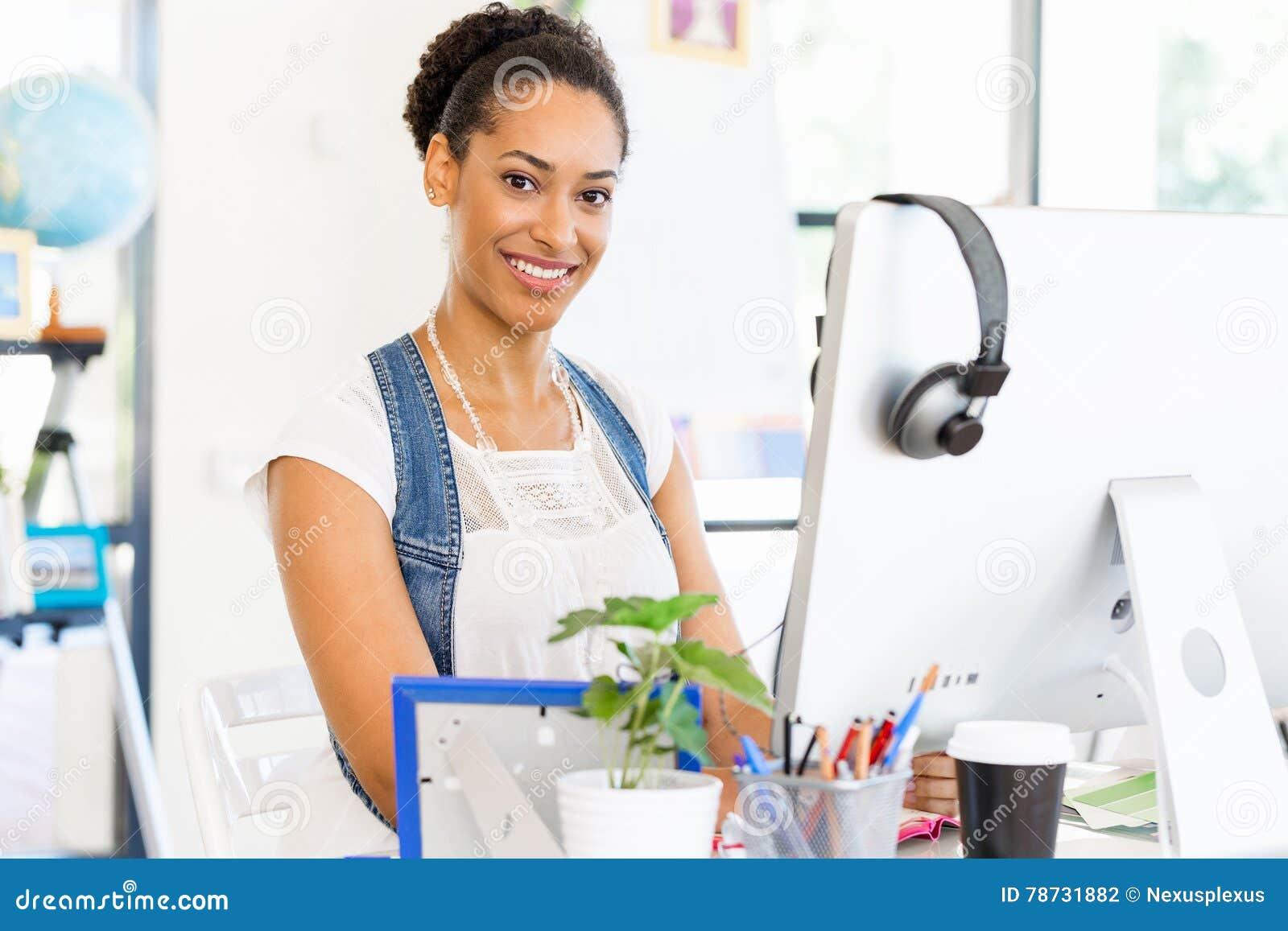 Stående av att le sammanträde för afro--amerikan kontorsarbetare i offfice