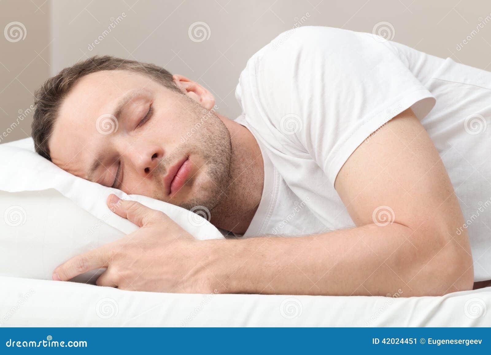 Stående av att sova den unga mannen i vit