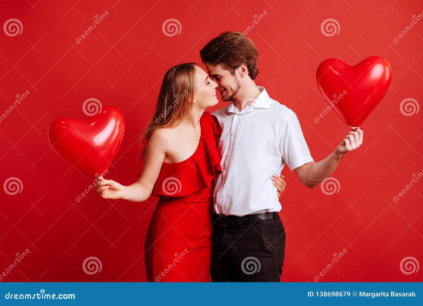 Stående av attraktiva unga par som poserar på röd bakgrund och rymmer ballonghjärta